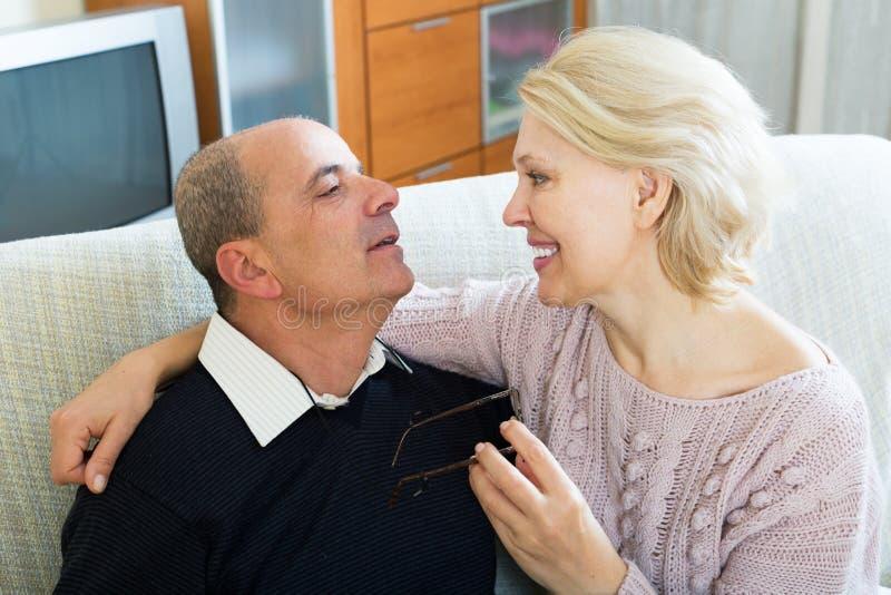 Пенсионеры пар совместно на софе дома стоковые фотографии rf