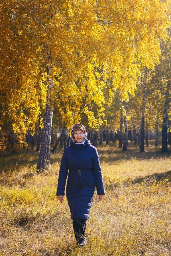 Пенсионер женщины идя в парк осени в осени стоковое фото rf