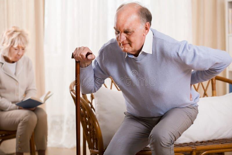 Пенсионер имея backache стоковые фото