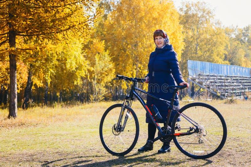 Пенсионный возраст женщины с велосипедом в осени стоковая фотография