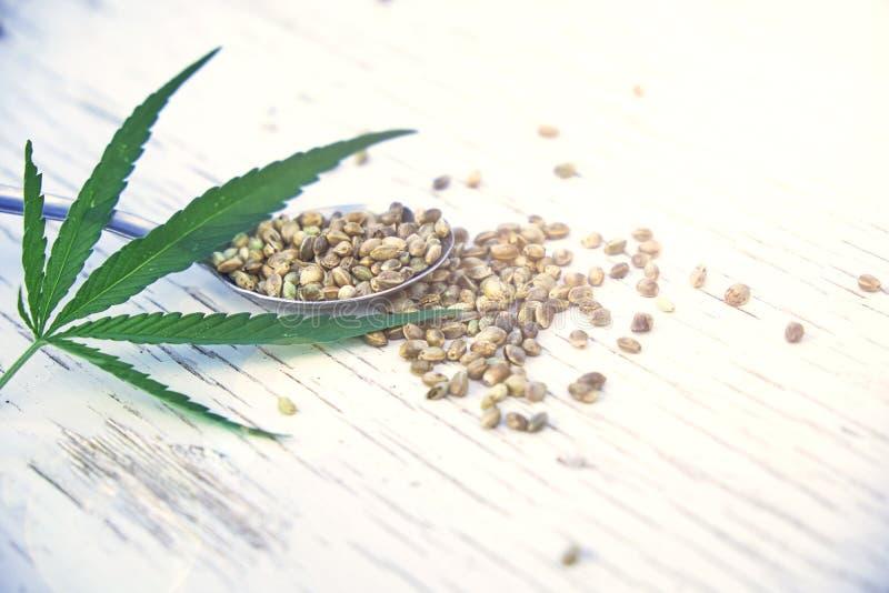 Пенька выходит на деревянную предпосылку, семена, выдержки масла конопли в опарниках стоковое изображение