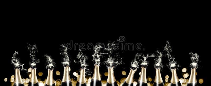 Пенящся и брызгающ шампанское разливает панораму по бутылкам стоковые фото