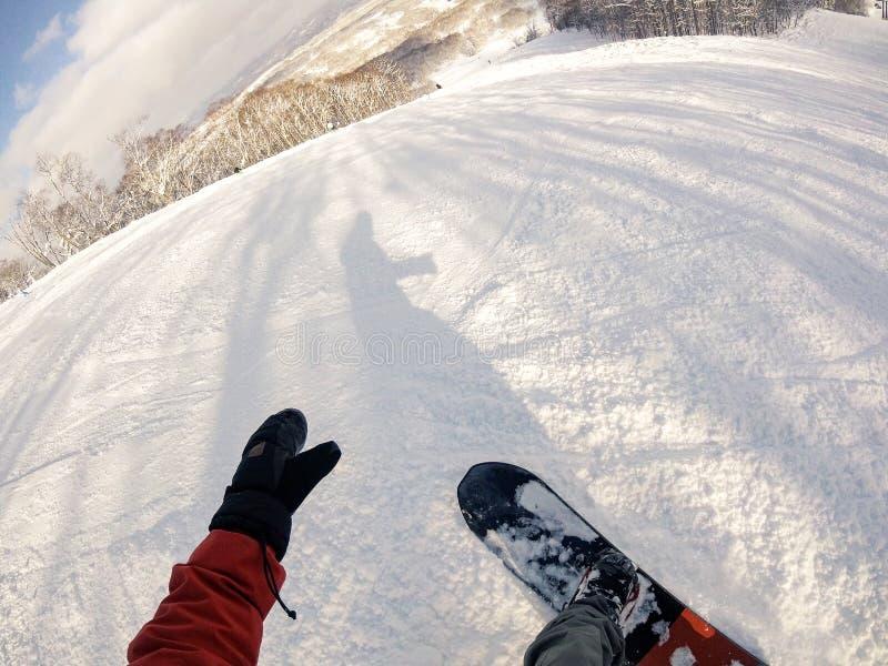 Первая перспектива человека snowboarder смотря вниз с горы стоковые фото