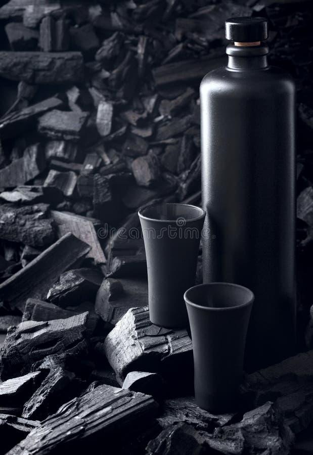 Первоначальная черная штейновая бутылка водки или текила и черной стопки На предпосылке угля Черный вариант творческо Позвольте н стоковые фото