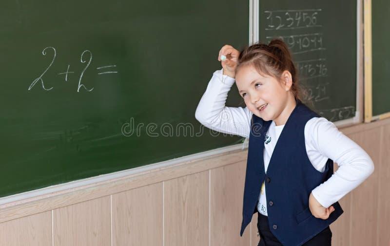 первый класс стоит у доски и решает пример в математике Вернуться в школу стоковое фото