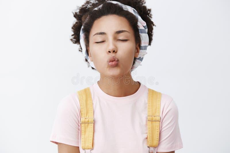 Первый никогда не забываемый поцелуй Портрет очаровывать и tendery стильной женщины с темной кожей в держателе и желтом цвете стоковое фото rf