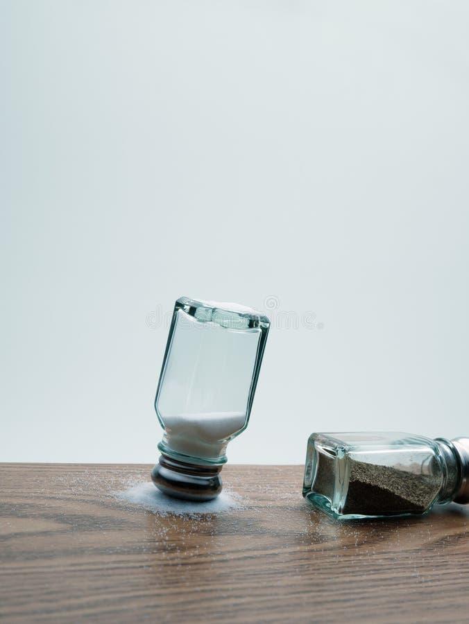 Перевернутый вверх дном солевой шейкер на пролитой соли с наклоненной над перцовым шейкером стоковая фотография