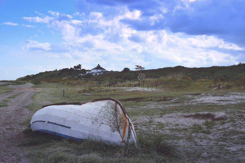 переворачиванная рыбацкая лодка на береге вереска близко стоковая фотография