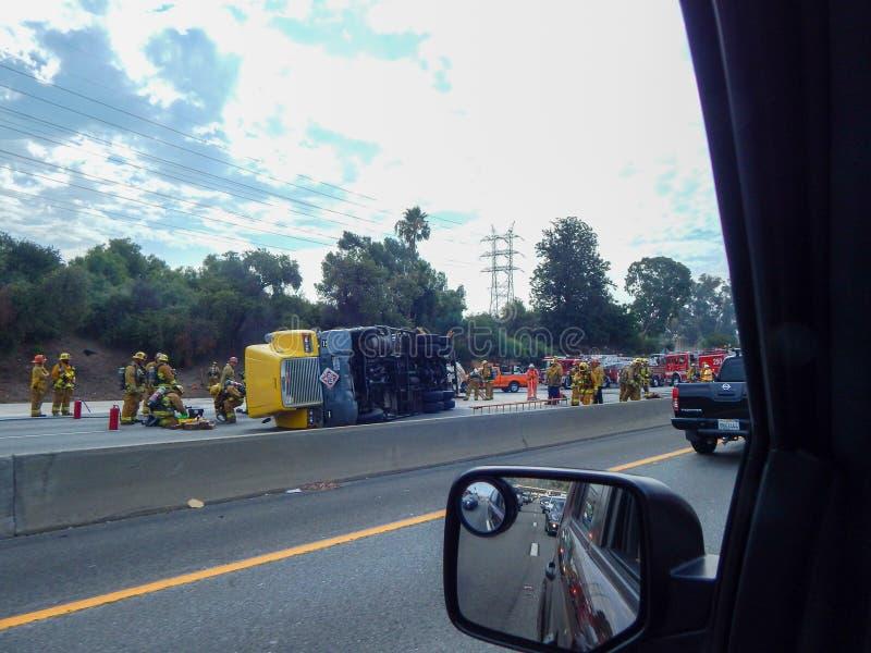 Переворачиванная тележка на скоростном шоссе 5 в Лос-Анджелесе с пожарными и другими первыми ответчиками стоковое фото