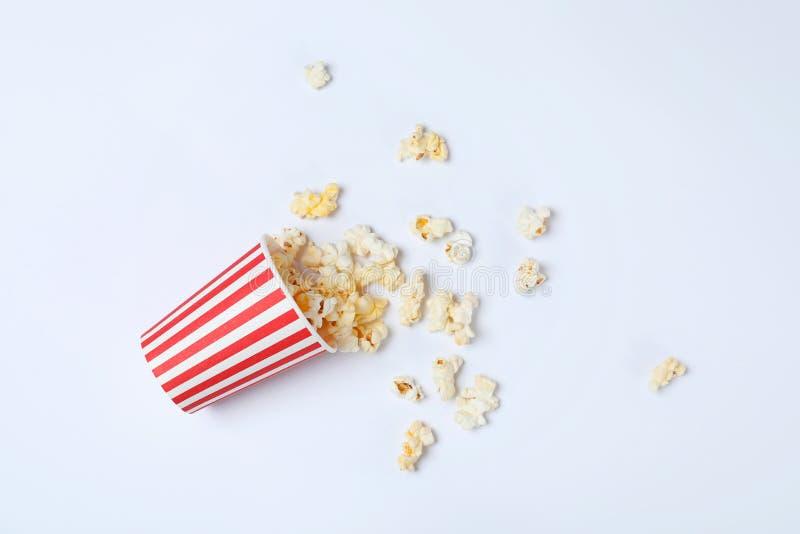 Переворачиванный бумажный стаканчик с вкусным попкорном на белой предпосылке стоковое изображение