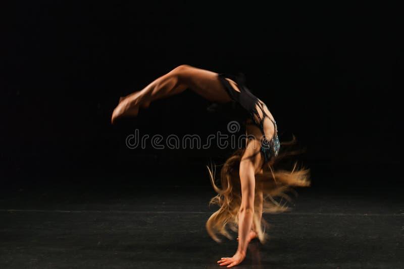 Переворот колесом гимнаста выполняя стоковая фотография