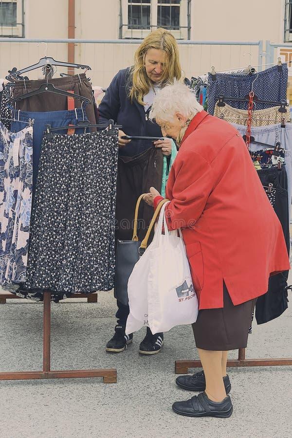 Переговор продаж на стойке одежды на еженедельном st рынка poelten стоковые фото