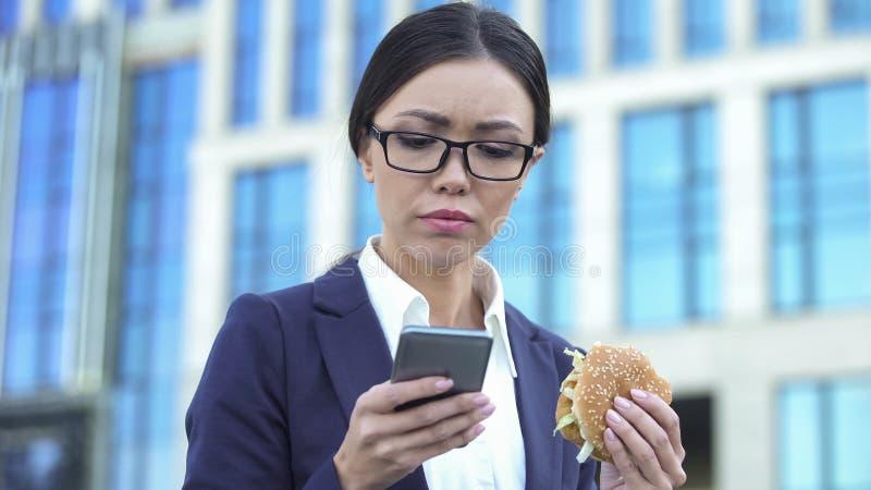 Перегружанный женский работник читая бургер удерживания деловых новостей, обеденное время стоковые фотографии rf