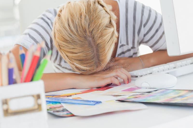 Перегружанный дизайнерский napping на ее столе стоковые изображения
