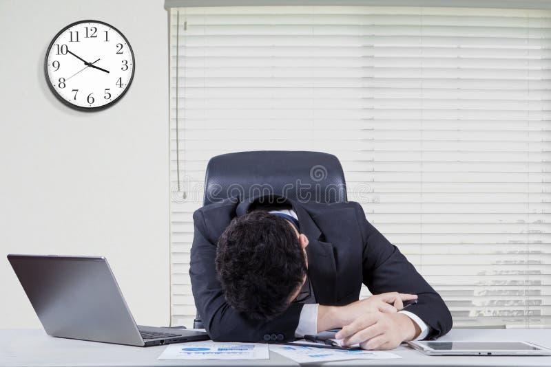 Перегружанный мужской работник спать в офисе стоковые фотографии rf