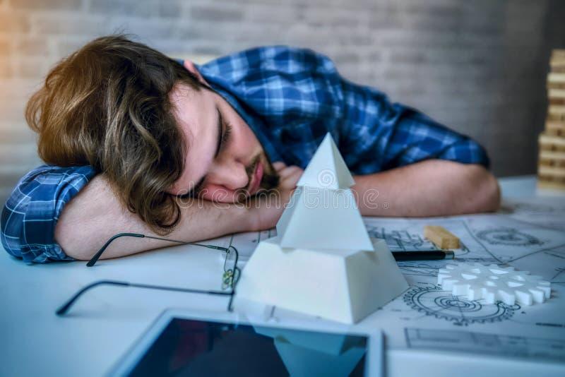 Перегрузки и сон человека инженерства работая на столе с частями светокопии механическими в офисе иметь плохие стресс и перегрузк стоковое изображение