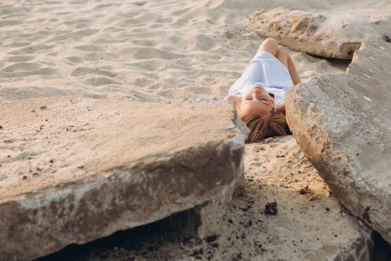 Передний план камней песка женщины лежа стоковая фотография rf
