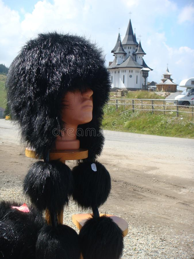 Передний план характерной меховой шапки Румынии с pompoms к оконечности и традиционными церков в расстоянии стоковые изображения rf
