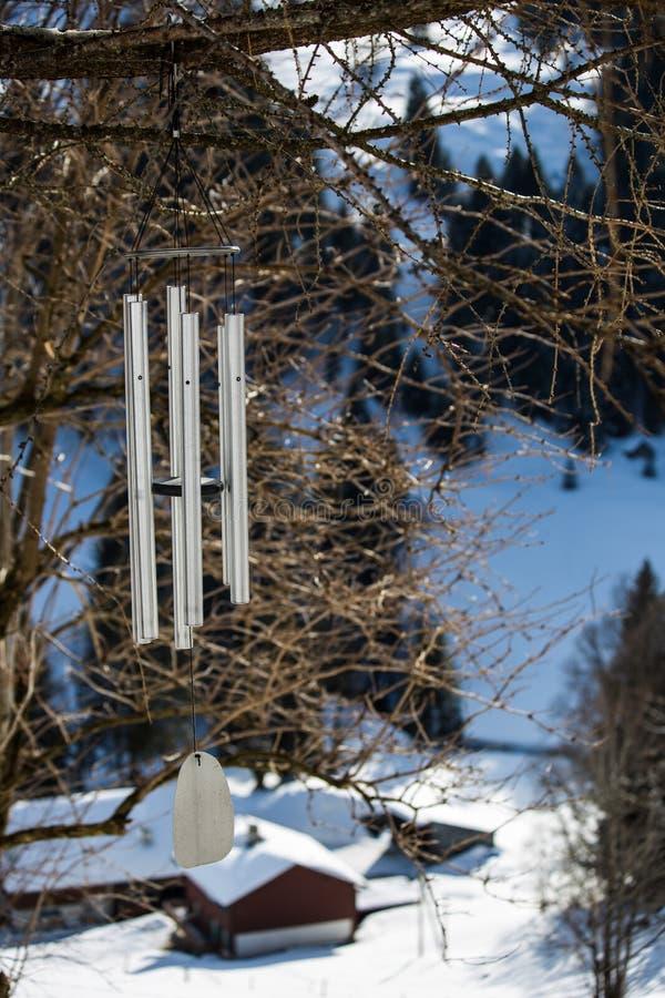 Перезвон ветра Minimalistic стальной повешенный на дереве в mountans стоковое изображение