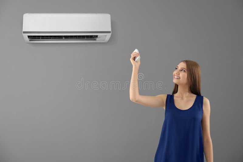 Переключение молодой женщины на кондиционере воздуха стоковая фотография