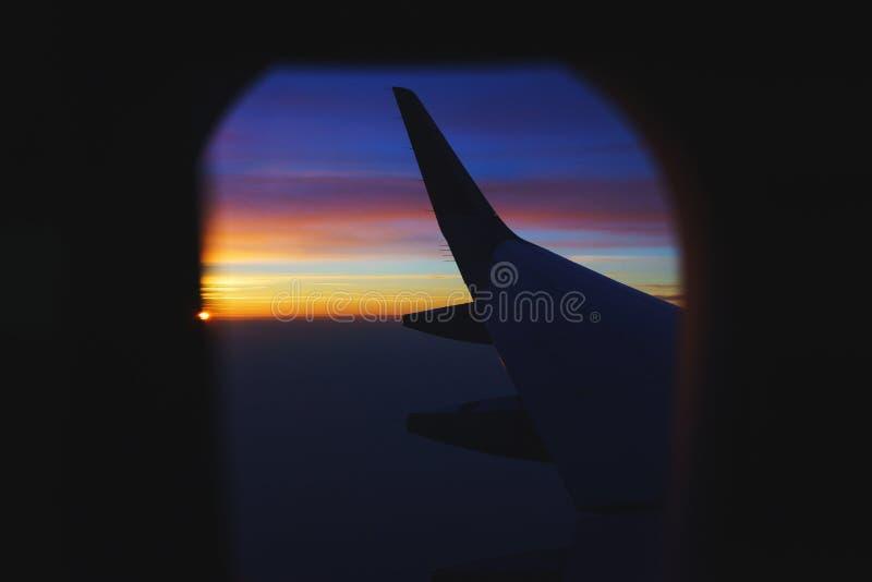 Перемещать плоскостью Взгляд от окна к облакам и рассвету стоковые фото