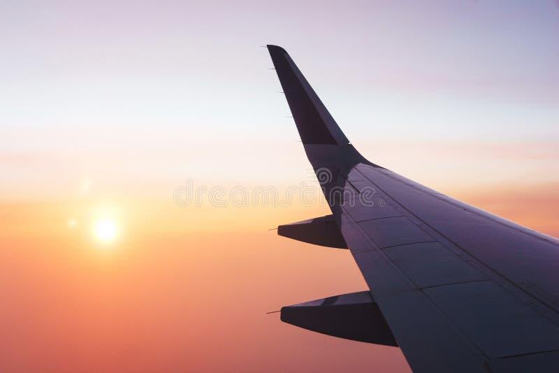Перемещать плоскостью Взгляд от окна к облакам и рассвету стоковая фотография