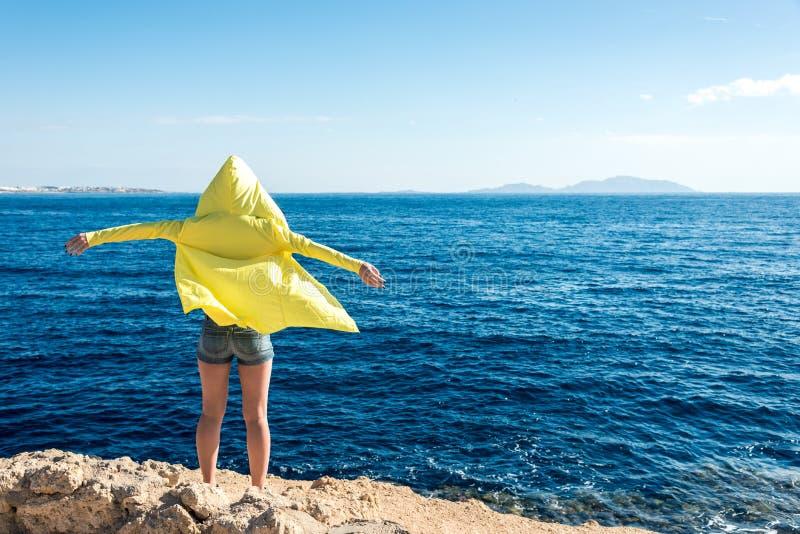 Перемещение и отдых, девушка в желтой куртке стоят против голубого моря с ее оружиями распространенными к сторонам стоковое изображение