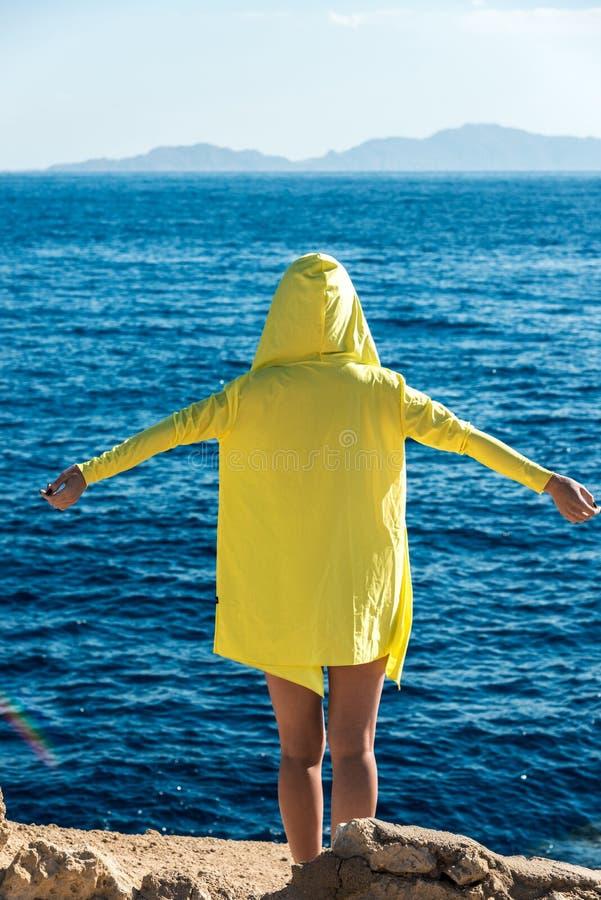 Перемещение и отдых, девушка в желтой куртке стоят против голубого моря с ее оружиями распространенными к сторонам стоковые фотографии rf