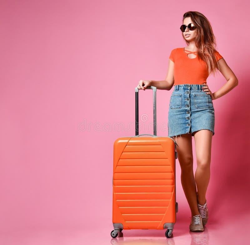 Перемещение и туризм концепции ноги девушки с красным чемоданом около белой пустой кирпичной стены стоковые изображения rf