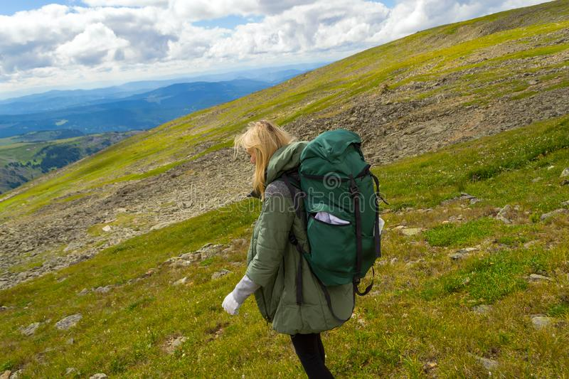 Перемещение маленькой девочки с большим зеленым рюкзаком идет вниз с холма на утесах к зеленым полям в названных горах altai sarl стоковые фотографии rf