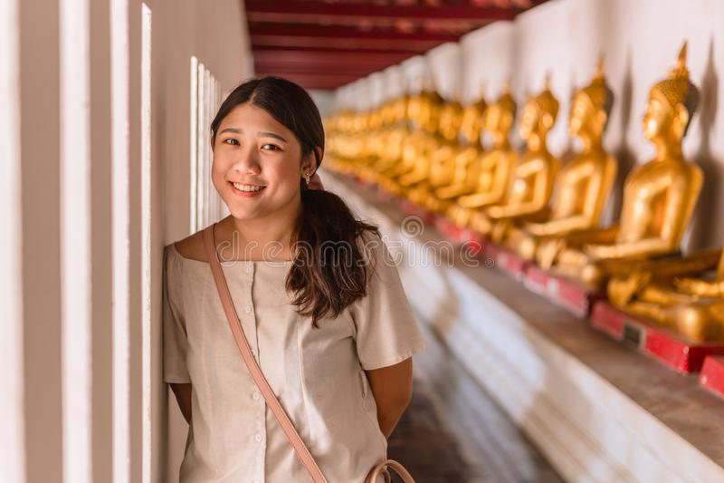 Перемещение милой азиатской предназначенной для подростков улыбки счастливое в виске с предпосылкой строки Будды стоковые фотографии rf