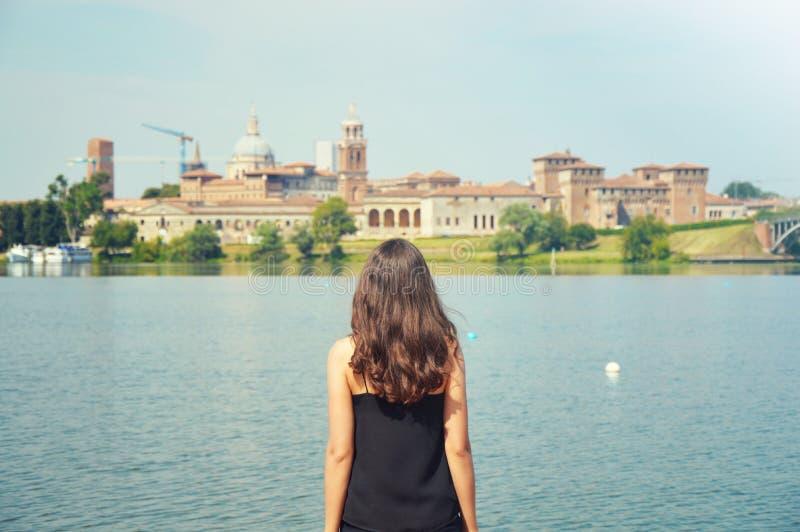Перемещение молодой женщины к Европе Счастливый турист в Mantua смотря городской пейзаж Жизнерадостный путешественник девушки брю стоковая фотография