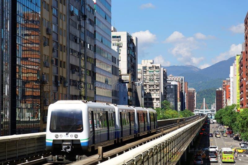 Перемещение поезда метро на повышенных рельсах линии Wenhu системы MRT Тайбэя офисом возвышается под голубым ясным небом стоковое фото