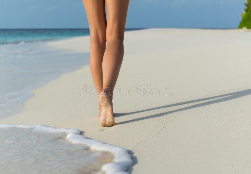 Перемещение пляжа - женщина идя на пляж песка выходя следы ноги в песок стоковая фотография rf