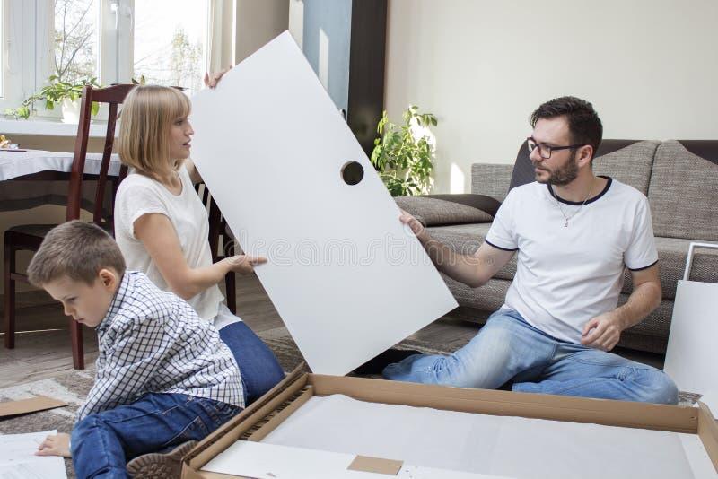 Переплетать семьи мебели Мама и папа складывают мебель Мальчик ребенка осторожно читает инструкции по монтажу стоковое изображение