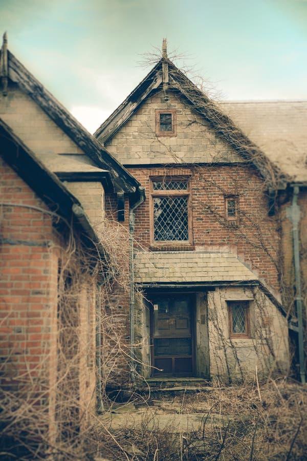 Перерастанный особняк кирпича на зимний день стоковая фотография