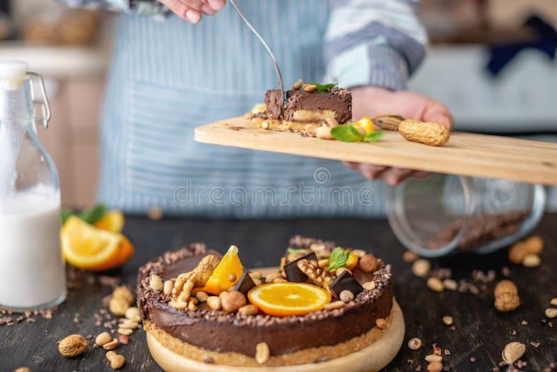Перерывы руки с вилкой часть шоколадного торта с апельсином и гайками Десерты концепции здоровые сырцовые для еды vegan стоковые изображения rf