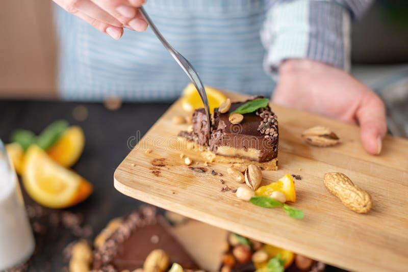 Перерывы руки с вилкой часть шоколадного торта с апельсином и гайками Десерты концепции здоровые сырцовые для еды vegan стоковая фотография rf