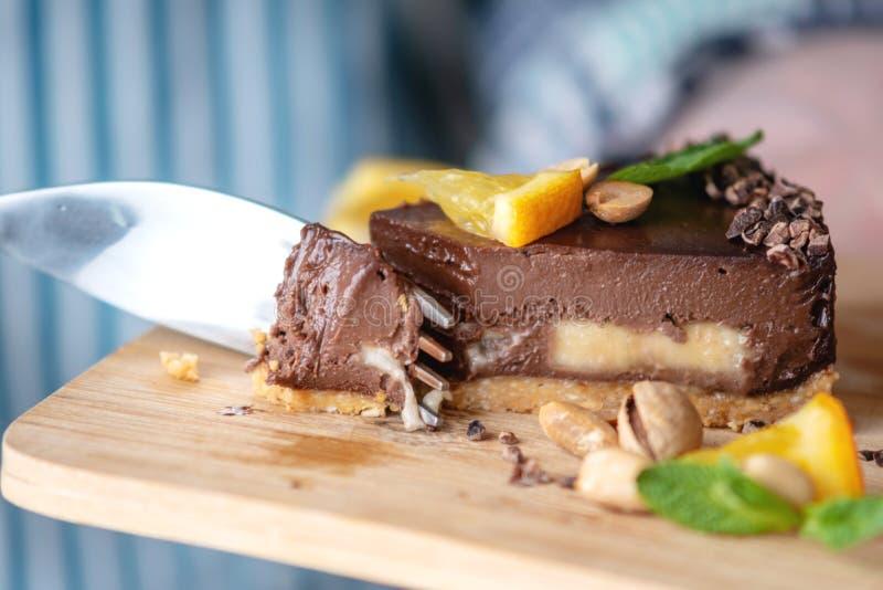 Перерывы руки с вилкой часть шоколадного торта с апельсином, листьями мяты и гайками r стоковые фотографии rf