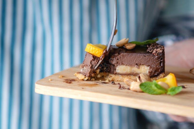 Перерывы руки с вилкой часть шоколадного торта с апельсином, листьями мяты и гайками r стоковое фото