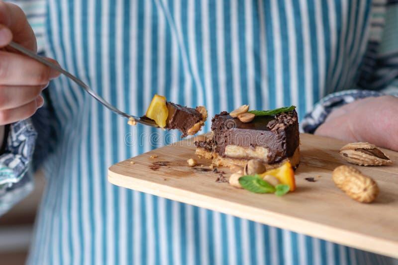 Перерывы руки с вилкой часть шоколадного торта с апельсином, листьями мяты и гайками r стоковые изображения