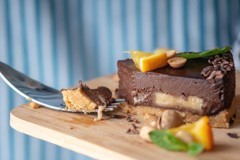 Перерывы руки с вилкой часть шоколадного торта с апельсином, листьями мяты и гайками r стоковое изображение rf
