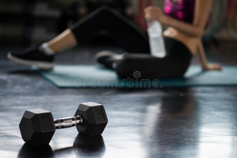 Перерыв женщины после тренировки гантели в спортзале стоковое фото rf
