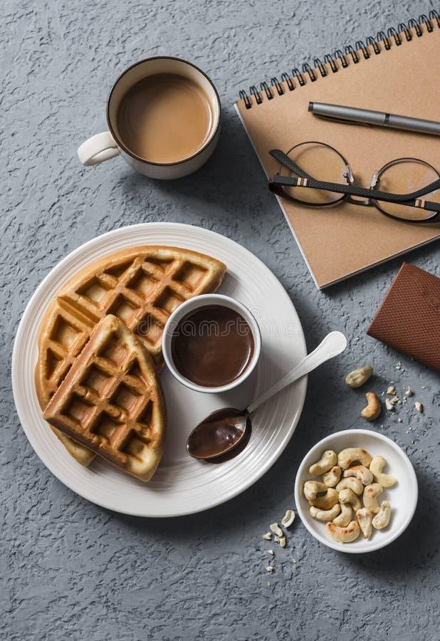 Перерыв на чашку кофе в рабочем месте Кофе и венские waffles с соусом шоколада на серой предпосылке стоковое фото rf