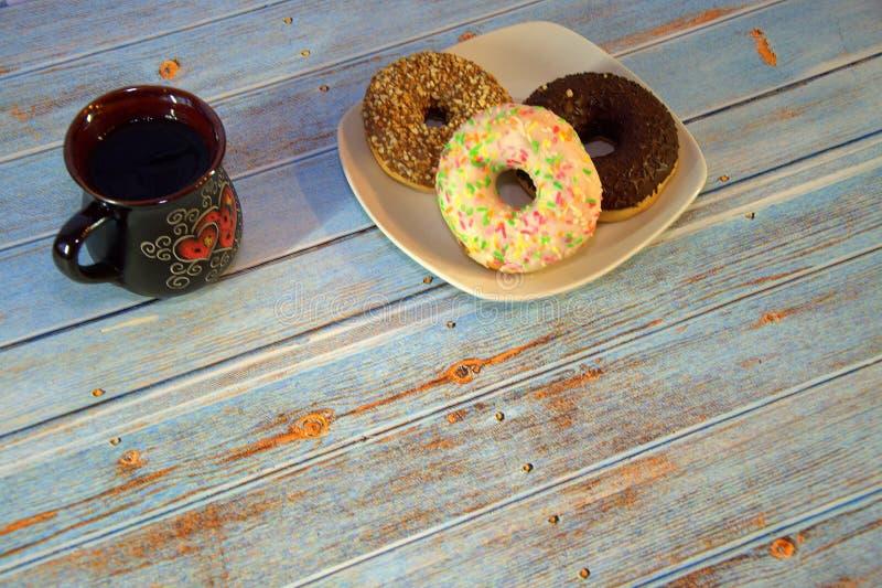 Перерыв на чашку кофе, donuts с замороженностью на плите и керамическая кружка с чаем : стоковое изображение