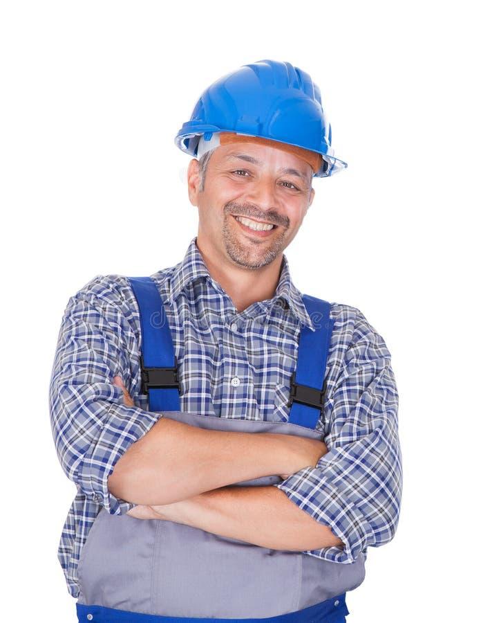 Пересеченные оружия счастливого работника физического труда стоящие стоковая фотография rf