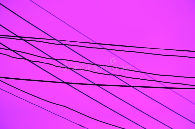 Пересеченные провода над темной предпосылкой лаванды стоковое фото