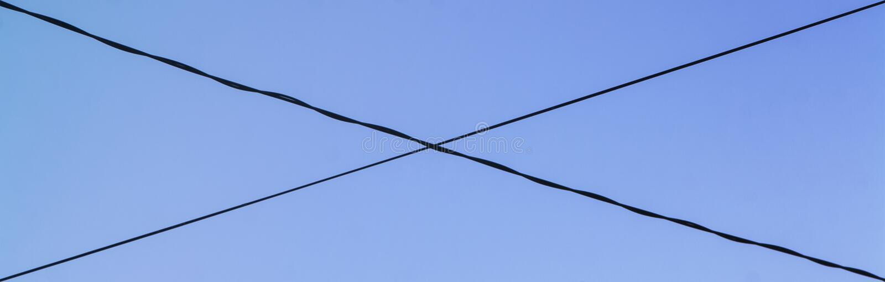 Пересеченные провода против голубого неба стоковые фото
