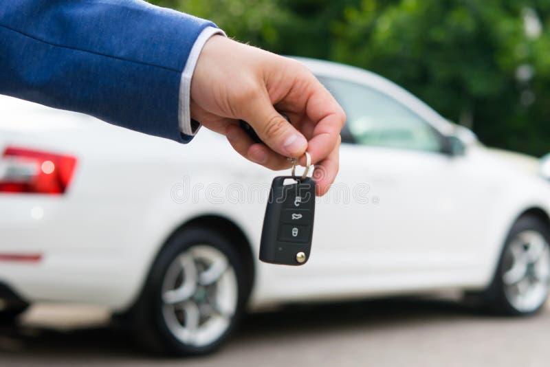 Переход автомобиля к новому владельцу для денег, ключи зажигания в руке менеджеров стоковые фотографии rf