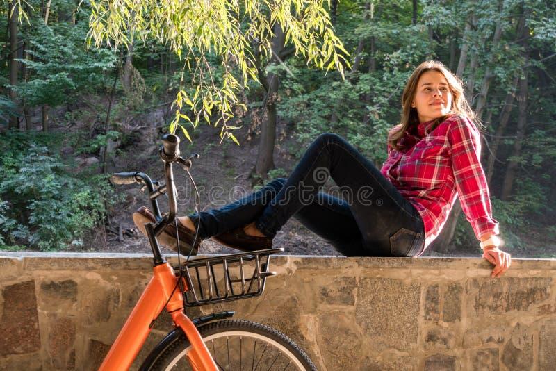 Переход велосипеда вопроса экологический Молодая кавказская женщина в джинсах и студенте рубашки сидит отдыхать в парке около озе стоковое изображение